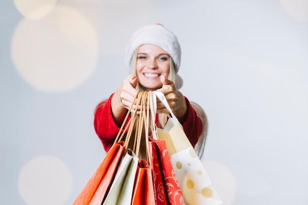 Kobieta w santa kapeluszu z torba na zakupy