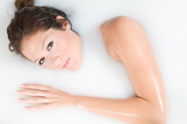 Kobieta w saunie lub spa podczas kąpieli w mleku