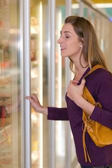 Kobieta w sekcji zamrażarki w supermarkecie