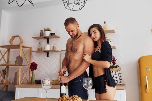 Kobieta w seksownej czarnej bieliźnie z mężem w kuchni.