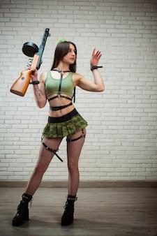 Kobieta w seksownym radzieckim mundurze wojskowym z pistoletem maszynowym ppsz-41 w krótkiej spódniczce i skórzanych pasach, mundur ii wojny światowej związku radzieckiego