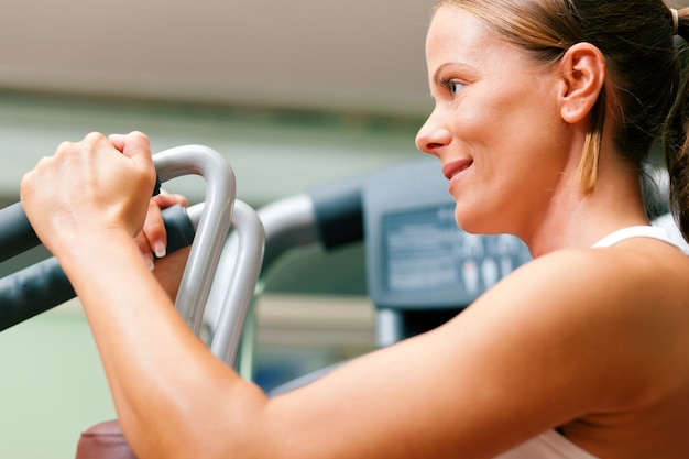 Kobieta w siłowni na maszynie