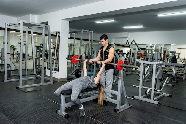 Kobieta w siłowni, praca ze sztangą z pomocą instruktora