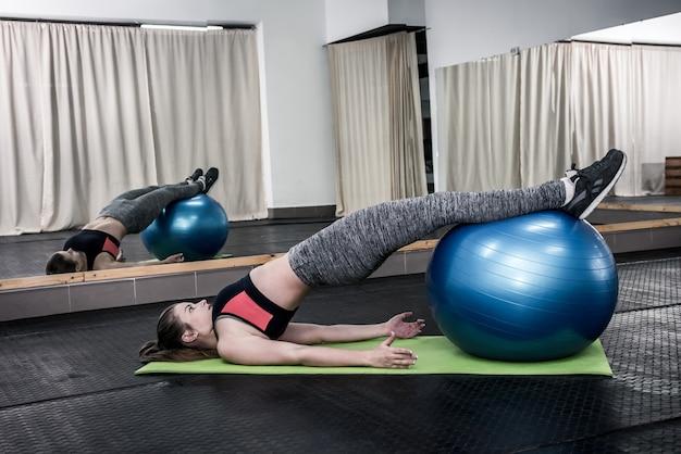 Kobieta w siłowni wykonywanie ćwiczeń z dużą piłką