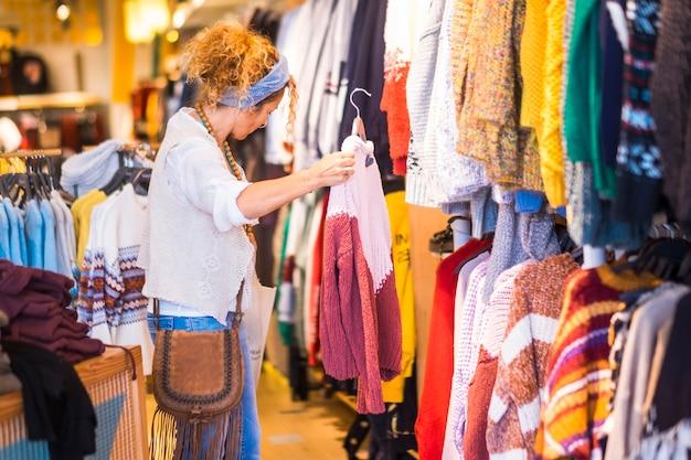 Kobieta w sklepach z ubraniami w kompulsywnej działalności zakupowej - modni ludzie styl życia mody - koncepcja okazji sprzedaży centrum handlowe ze zniżkami i ludzie kupujący