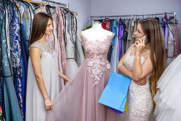 Kobieta w sklepie odzieżowym dzwoniąc i patrząc na sukienkę na manekinie
