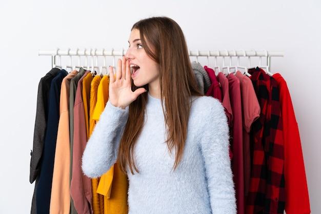 Kobieta w sklepie odzieżowym z dużą ilością ubrań z tyłu