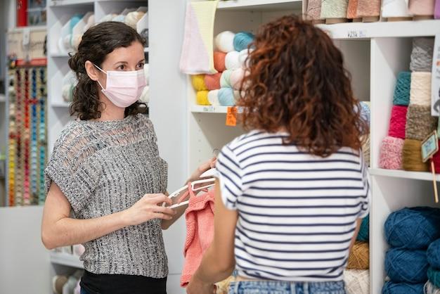 Kobieta w sklepie w masce pomaga klientowi wybrać prezent