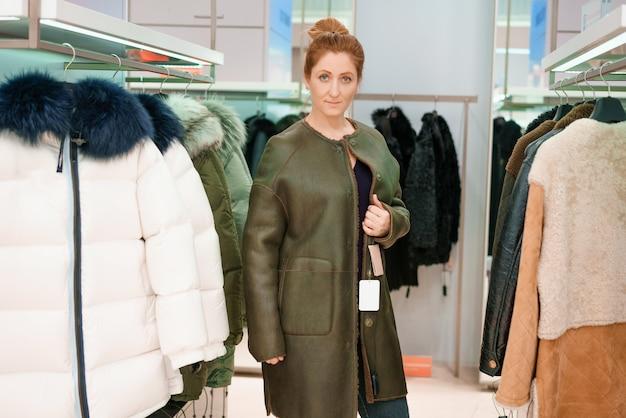 Kobieta w sklepie wybiera kurtkę zimową