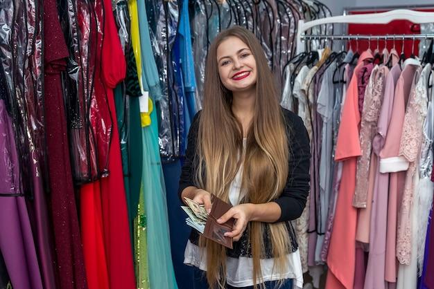 Kobieta w sklepie z sukniami pozuje z portfelem