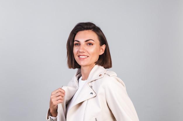 Kobieta w skórzanej kurtce na szarej ścianie