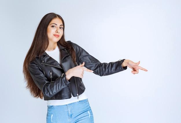 Kobieta w skórzanej kurtce pokazując coś po prawej stronie.