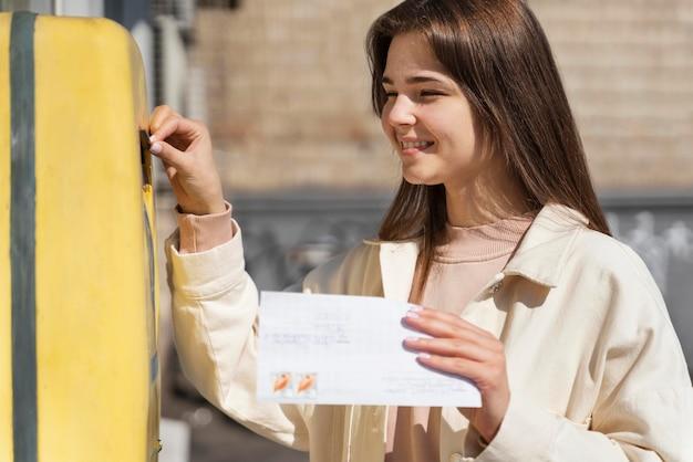 Kobieta w skrzynce pocztowej z kopertą