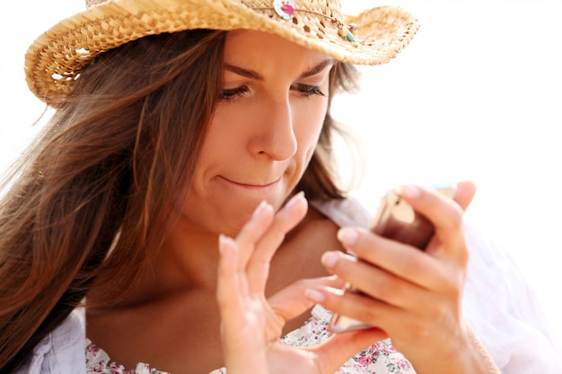 Kobieta w słomkowym kapeluszu gospodarstwa telefon