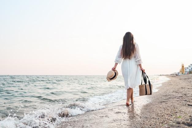 Kobieta w słomkowym kapeluszu i białej sukni na tropikalnej plaży z brązową torbą.