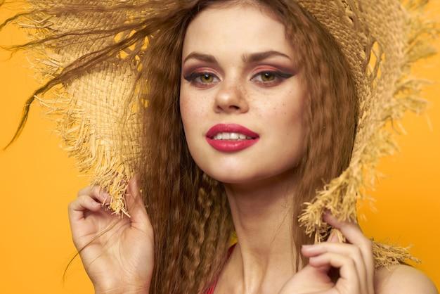 Kobieta w słomkowym kapeluszu jasny makijaż lato styl życia zabawa żółte tło