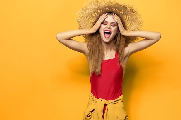 Kobieta w słomkowym kapeluszu jasny makijaż lato styl życia zabawa żółty.