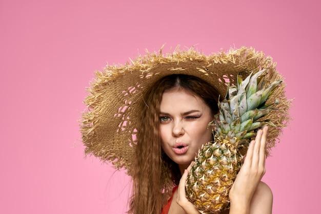 Kobieta w słomkowym kapeluszu na nas owoce zabawne kosmetyki różowe tło.