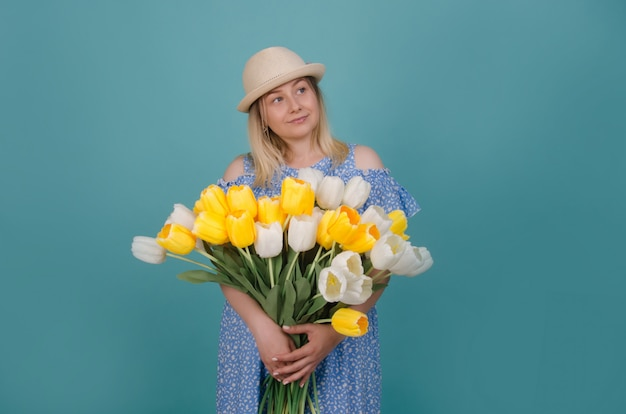Kobieta w słomkowym kapeluszu na sobie niebieską sukienkę z białych i żółtych tulipanów w jej ręce. koncepcja lato i wiosna.