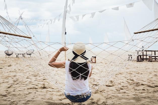 Kobieta w słomkowym kapeluszu relaks w hamaku