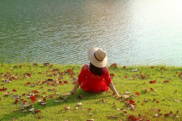Kobieta w słomkowym kapeluszu relaksuje się samotnie nad słonecznym jeziorem