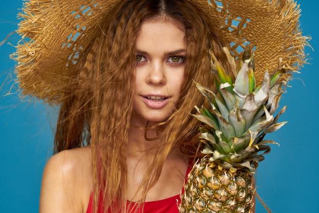 Kobieta w słomkowym kapeluszu z ananasem w dłoniach, czy jest to zabawne niebieskie tło egzotycznych owoców