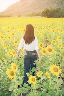 Kobieta w słonecznikowe pole. zdrowy produkt spożywczy.