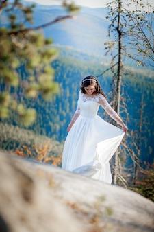 Kobieta w ślubnej sukni pozuje w naturze