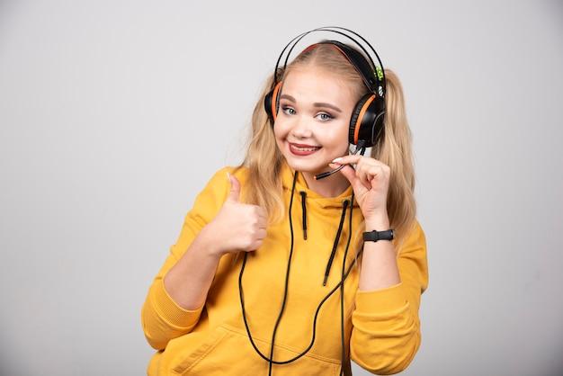 Kobieta w słuchawkach daje aprobaty na szarym tle.