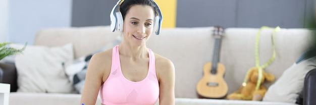 Kobieta w słuchawkach i dresie robi notatki na notebooku podczas internetowych treningów odchudzania