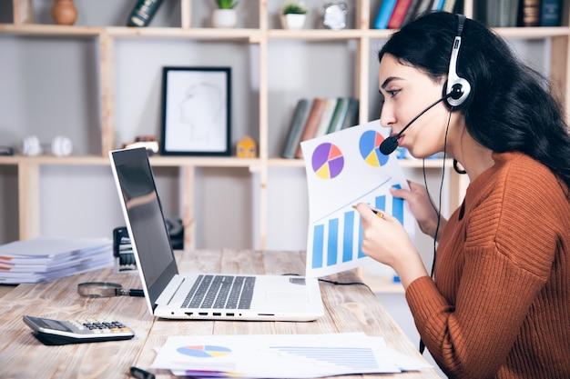 Kobieta w słuchawkach mówi w wykresie ręki komputera