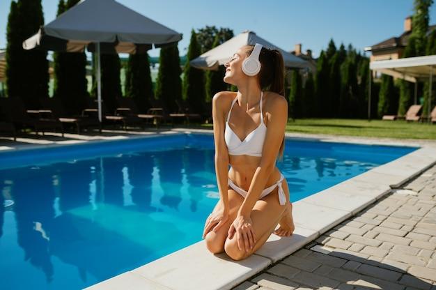 Kobieta w słuchawkach pije koktajl na basenie