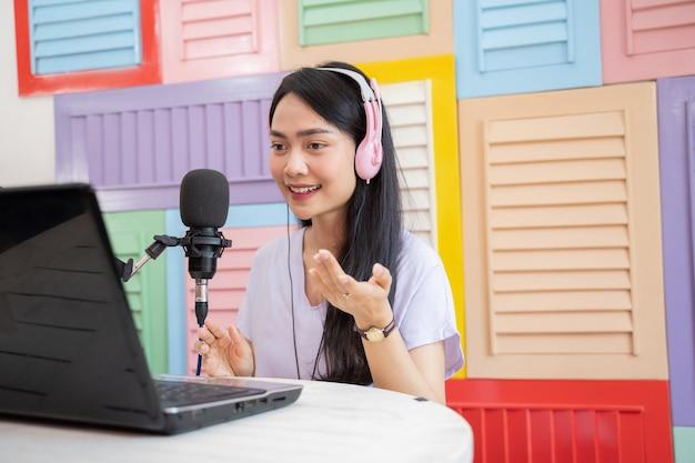 Kobieta w słuchawkach rozmawiająca przed mikrofonem z gestem ręki