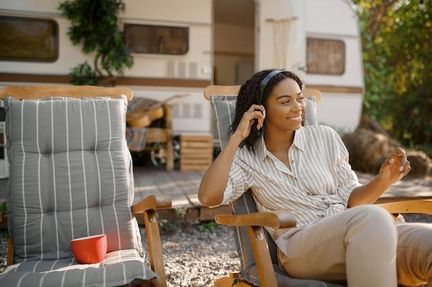 Kobieta w słuchawkach siedzi w pobliżu kampera, biwakuje w przyczepie. para podróżuje furgonetką, romantyczne wakacje w kamperze, wycieczki kamperem w kamperze, obóz