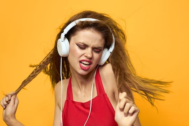 Kobieta w słuchawkach słuchanie muzyki czerwona koszulka t shirt emocje moda żółte tło styl życia