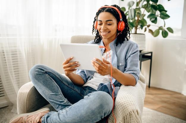 Kobieta w słuchawkach, słuchanie muzyki z komputera typu tablet.