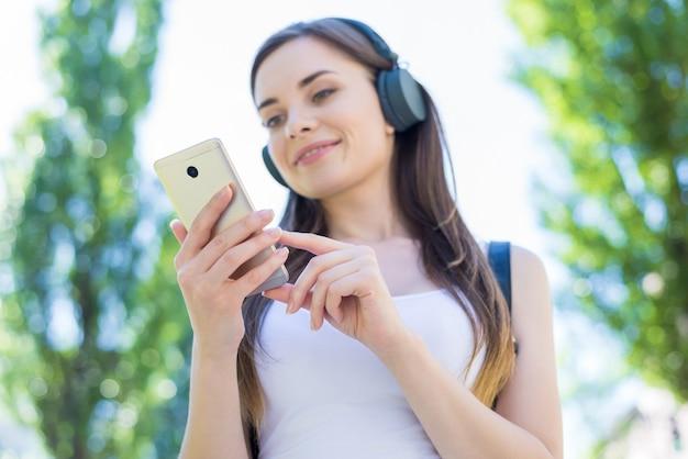 Kobieta w słuchawkach za pomocą telefonu komórkowego