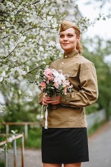 Kobieta w sowieckim mundurze wojskowym obok kwitnącego drzewa