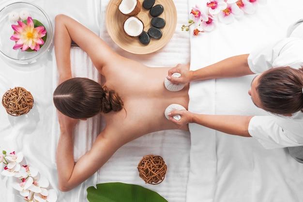 Kobieta w spa masaż tajski holowania, koncepcja zabiegów kosmetycznych. kwiaty orchidei i lotosu, kamienie kokosowe i woreczki z ziołami