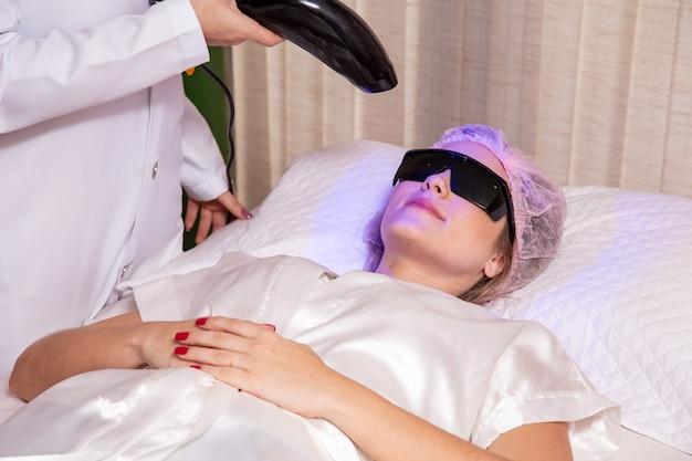 Kobieta w spa robi terapię światłem led.