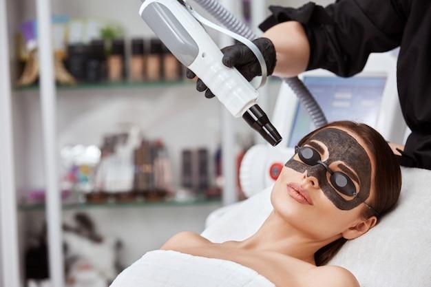 Kobieta w spa z czarną maską węglową i kosmetologiem z laserem w pobliżu twarzy, kopia przestrzeń, urocza kobieta po odmłodzeniu przez kosmetyczkę