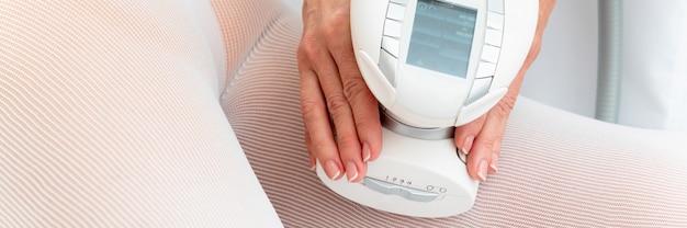 Kobieta w specjalnym białym garniturze zaczyna masaż antycellulitowy na nogi w salonie spa. lpg i zabieg modelowania sylwetki w klinice.