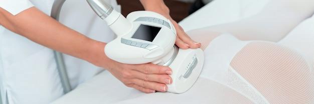 Kobieta w specjalnym białym garniturze zaczyna masaż antycellulitowy w salonie spa. lpg i zabieg modelowania sylwetki w klinice.
