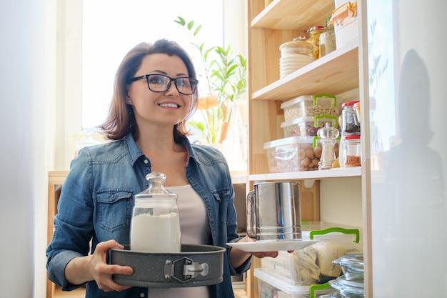 Kobieta w spiżarni z artykułami spożywczymi, drewniany stojak do przechowywania żywności w kuchni