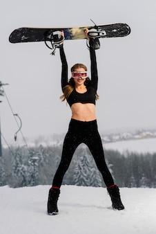 Kobieta w sporcie nosić snowboarder pozowanie w okulary z snowboard