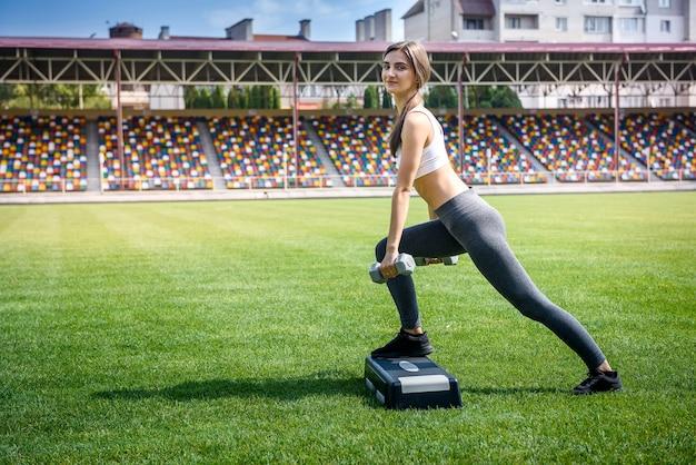 Kobieta w sportowej na zielonej trawie wykonywania ćwiczeń na odchudzanie
