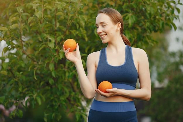 Kobieta w sportowej posiada owoce