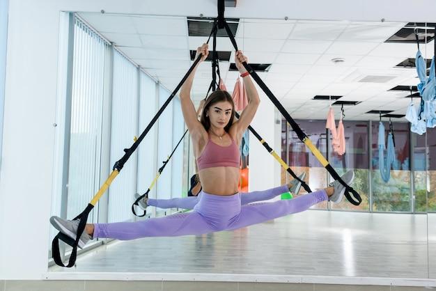 Kobieta w sportowej pracy ze sprzętem trx i robi nogi ćwiczenia w siłowni fitness. trening femamle dla zdrowego stylu życia
