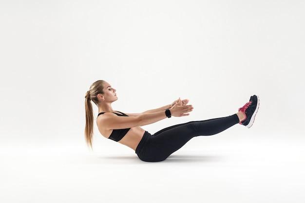 Kobieta w sportowej robi ćwiczenia pilates