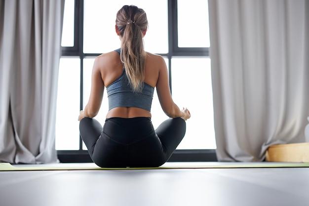 Kobieta w sportowy top i legginsy, praktykuje jogę w domu, siedząc w pozycji lotosu, praktykuj medytację. widok z tyłu